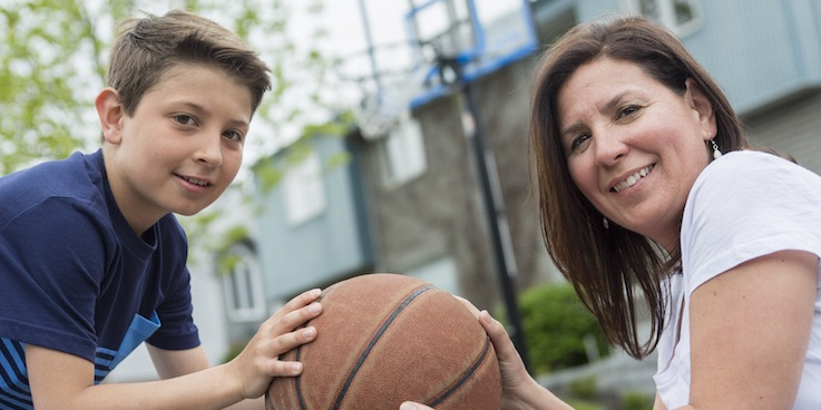 Image of mother and son holding basketball