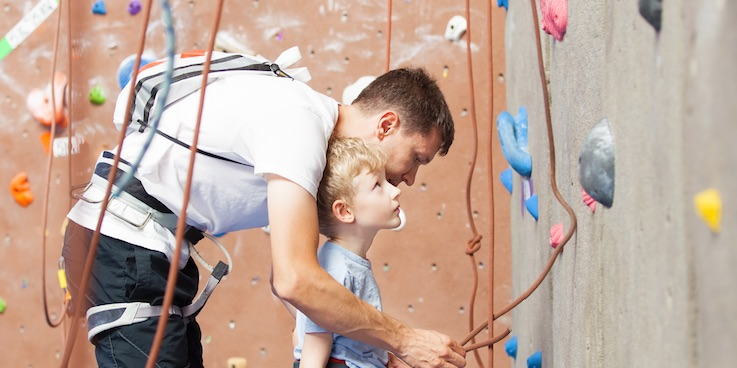 Young boy looking at climbing wall